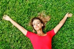 Junge Frau im roten Kleid, das auf Gras liegt Lizenzfreie Stockbilder
