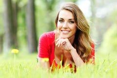 Junge Frau im roten Kleid, das auf Gras liegt Lizenzfreie Stockfotografie