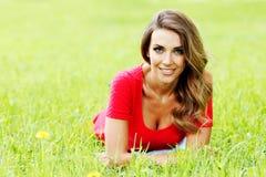 Junge Frau im roten Kleid, das auf Gras liegt Stockfoto