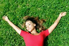Junge Frau im roten Kleid, das auf Gras liegt Lizenzfreies Stockbild
