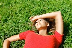 Junge Frau im roten Kleid, das auf Gras liegt Lizenzfreie Stockfotos