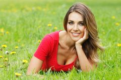 Junge Frau im roten Kleid, das auf Gras liegt Stockfotos