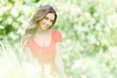 Junge Frau im roten Kleid, das auf Gras sitzt Stockbild
