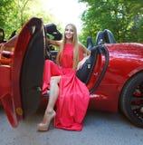 Junge Frau im roten Kleid, das in einem Sportauto stationiert Lizenzfreie Stockfotos