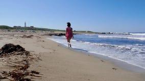 Junge Frau im roten Kleid, das entlang den leeren Strand l?uft Starke Wellen spritzen und wickeln den Schlag Leuchtturm auf dem H stock footage