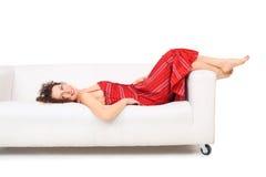 Junge Frau im roten Kleid liegt auf weißem Sofa Lizenzfreie Stockfotografie