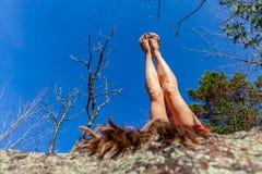 Junge Frau im roten Kleid zeigt ihre Beine bei auf ihr zurück niederlegen stockbild
