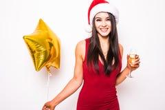 Junge Frau im roten Kleider- und Sankt-Weihnachtshut mit lächelndem und trinkendem Champagner des Goldsternförmigem Ballons Stockfotos
