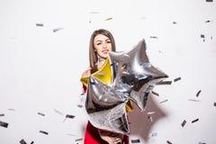 Junge Frau im roten Kleiderholding-Sternballon mit Fliegenkonfettis an der Partei Lizenzfreie Stockbilder