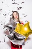 Junge Frau im roten Kleiderholding-Sternballon mit Fliegenkonfettis an der Partei Lizenzfreie Stockfotografie