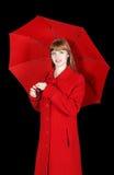 Junge Frau im roten Mantel mit Regenschirm Lizenzfreies Stockfoto
