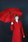 Junge Frau im roten Mantel steht mit Regenschirm Stockfotografie