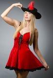 Junge Frau im roten Minikleid und im Hut gegen Grau Stockbild