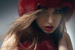 Junge Frau im roten Pelzhut Stockfotografie