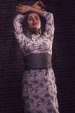 Junge Frau im schönen eleganten Kleid, das in einer Haltung mit den Händen obenliegend steht Stockfoto