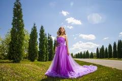 Junge Frau im schönen Kleid unter Bäumen Stockbild