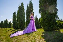 Junge Frau im schönen Kleid unter Bäumen Lizenzfreies Stockfoto