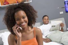 Junge Frau im Schlafzimmer unter Verwendung des Handys Stockbild