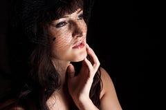 Junge Frau im schwarzen Hut mit Netz Stockfotografie