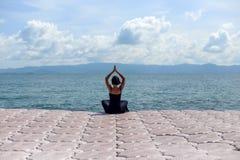 Junge Frau im schwarzen Kleid auf Pier im Meer Stockfotos