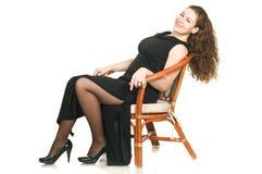 Junge Frau im schwarzen Kleid auf Stuhl stockbilder