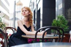 Junge Frau im schwarzen Kleid in den Cafés Lizenzfreies Stockbild