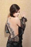 Junge Frau im schwarzen Kleid mit Karosserienkunst Stockfoto