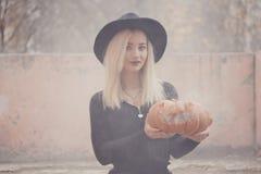 Junge Frau im schwarzen Mantel, der den Halloween-Kürbis mit dem weißen Rauche von innen kommt von ihm im Herbst hält stockfoto