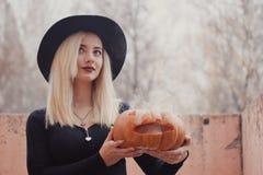 Junge Frau im schwarzen Mantel, der den Halloween-Kürbis mit dem weißen Rauche von innen kommt von ihm im Herbst hält lizenzfreies stockfoto
