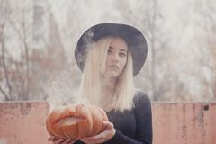 Junge Frau im schwarzen Mantel, der den Halloween-Kürbis mit dem weißen Rauche von innen kommt von ihm im Herbst hält stockbilder