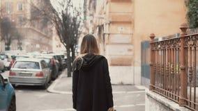 Junge Frau im schwarzen Mantel gehend in das alte Stadtteil Hintere Ansicht des Mädchens, welches die neue Stadt erforscht Langsa stock footage