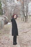Junge Frau im schwarzen Mantelstand auf dem Weg im Freien im Winter des Parkblickes zurück stockbild