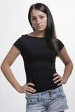 Reizender Brunette, der mit den Armen auf Hüften steht Stockbilder