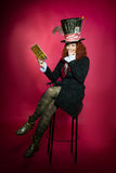 Junge Frau im Similitude des Hutmacherlesebuchsitzens Stockfotos
