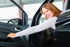Junge Frau im Sitz des Automobils im Auto-Vertragshändler Lizenzfreie Stockfotos