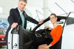Junge Frau im Sitz des Automobils im Auto-Vertragshändler Stockfotos