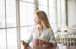 Junge Frau im sitzenden trinkenden Kaffee des Cafés, der den Smartphone heraus schaut das Fenster dreamful hält Stockfoto