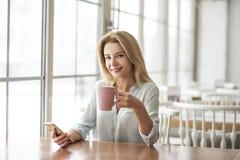 Junge Frau im sitzenden trinkenden Kaffee des Cafés, der den Smartphone schaut Kamera nett hält Lizenzfreie Stockfotos