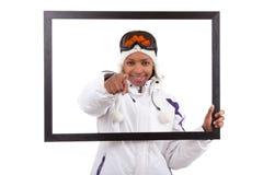 Junge Frau im Ski übersetzt das Anhalten eines Bilderrahmens Lizenzfreies Stockbild