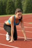 Junge Frau im Sport-Büstenhalter in Ausgangsposition Stockfotografie