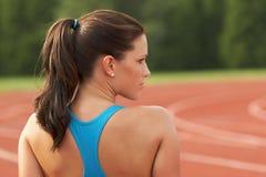 Junge Frau im Sport-Büstenhalter, der über Schulter schaut Lizenzfreie Stockbilder