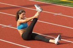 Junge Frau im Sport-Büstenhalter, der angehobenes Fahrwerkbein auf laufender Zahnstange ausdehnt Stockfotografie