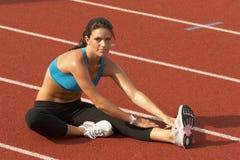 Junge Frau im Sport-Büstenhalter, der Fahrwerkbein-Muskeln auf Spur ausdehnt lizenzfreies stockfoto