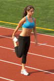 Junge Frau im Sport-Büstenhalter, der Oberschenkelmuskel ausdehnt Stockbild