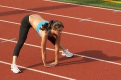 Junge Frau im Sport-Büstenhalter, der sich vorwärts lehnt und Kniesehnen ausdehnt Lizenzfreies Stockfoto