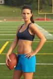 Junge Frau im Sport-Büstenhalter-Holding-Fußball mit der Hand auf Hüfte Lizenzfreie Stockbilder