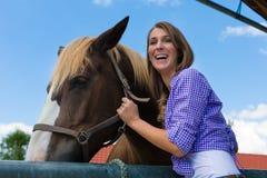 Junge Frau im Stall mit Pferd am Sonnenschein Lizenzfreies Stockfoto