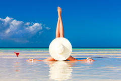 Junge Frau im Strohhut, der am tropischen Strand und am enjoyi legt Stockbild