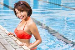 Junge Frau im Swimmingpool lizenzfreie stockfotos