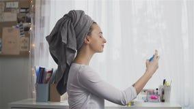 Junge Frau im Tuch unter Verwendung des Haarsprays stock video footage